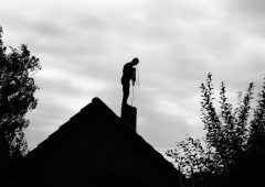 Contour of a chimney sweep, silhouetted against the light.Black and white photo.